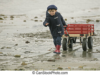 small boy with red wagon - small boy pulling his large red...