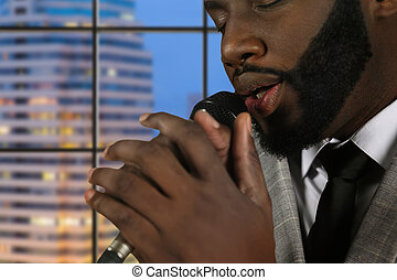 Afro singer with eyes closed. Bearded vocalist on evening...