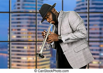 Man in hat playing trumpet. Darkskinned trumpeter on evening...