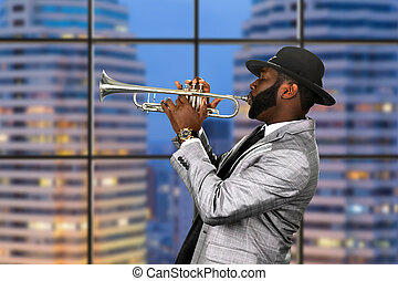 Afro trumpeter in black hat. Trumpet performance on...