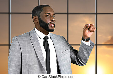 Afro businessman points his finger. Smiling executive on...