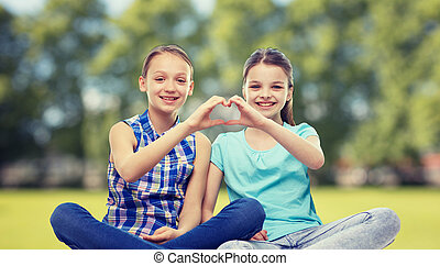 happy little girls showing heart shape hand sign - people,...