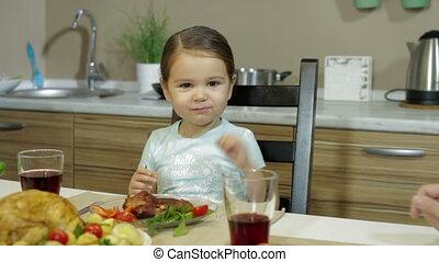 A Little girl having family dinner