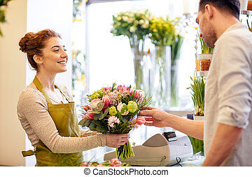 smiling florist woman and man at flower shop - people,...