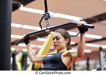 woman flexing arm muscles on cable machine in gym - sport,...