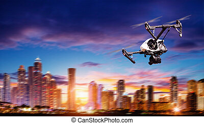Drone silhouette flying above modern city panorama at night