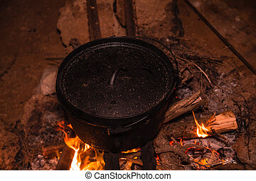 Cooking meal in cauldron on burning campfire at night.