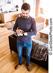 Man working from home using smart watch, living room -...