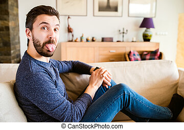 Man at home sitting on sofa using smart watch, making funny...