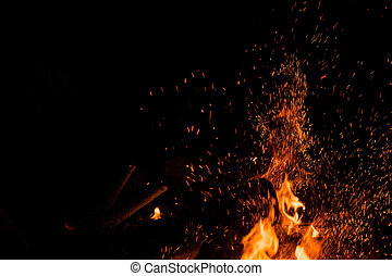 Sparks bounce off from a bonfire at night after a log thrown...