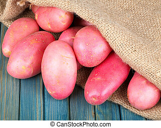 red potatoes in burlap sack on a blue wooden table