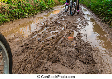 Bicycle ride through muddy dirt road.
