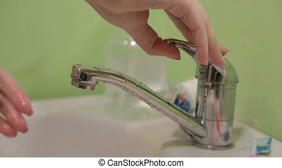 A person washing and rinsing off their hands in the bathroom sink.