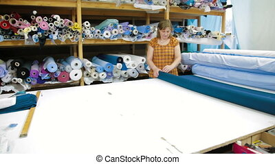 Female tailor choosing textile for sewing shirt
