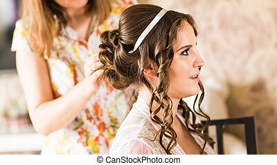 Hair stylist makes the bride before a wedding - Hair stylist...