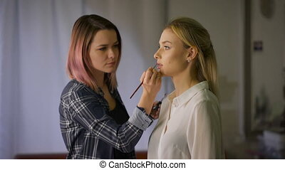 attractive woman having lip gloss make up applying in salon....