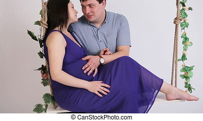 Pregnant woman with her husband on a swing. - Pregnant woman...