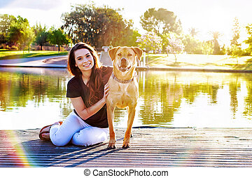 Girl and Dog at Park Sunflare - Pretty young woman and her...