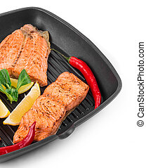 Fried salmon fillet in pan with lemon Whole background