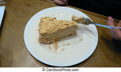 Cake being cut with fork on white plate and eaten - Piece of...