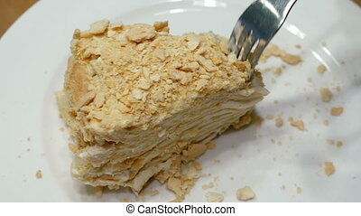 Cake being cut with fork on white plate and eaten
