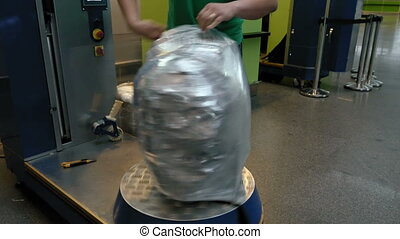 Wrapping luggage baggage bag at airport terminal - Wrapping...
