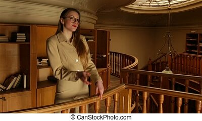 On a warm pale light in the old library beautiful young woman in suit and glasses choose a book to read