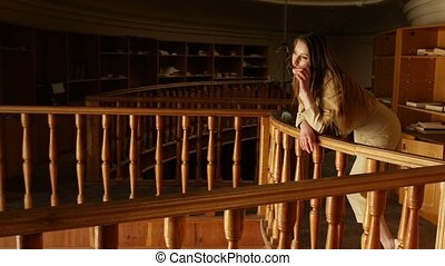 Attractive young business woman takes off glasses. Old vintage library on background