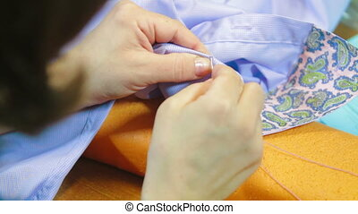 Female sewing on buttons to shirt
