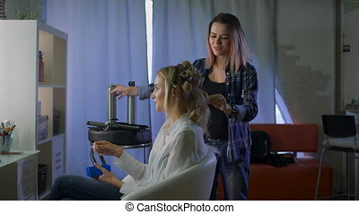 For a young beautiful blonde woman in a beauty salon doing hair style. A girl and a hairdresser