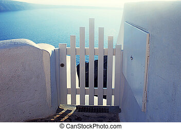 Small white fence gate in Oia on Santorini island, Greece -...