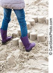 Little girl crushing mud pies