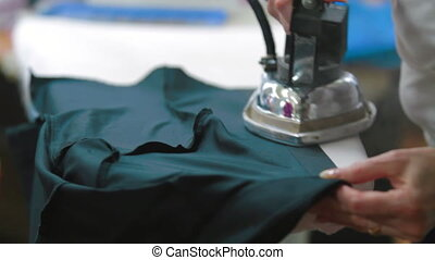 Female tailor stroking shirt with clothing iron - Machine...