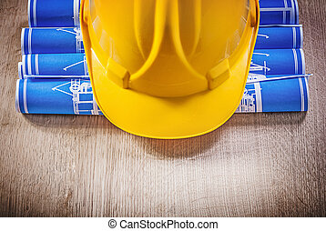 Wooden board with blue rolled up construction plans hard hat