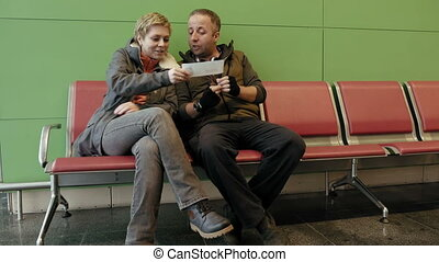 Couple waiting at airport terminal with tickets - Family...