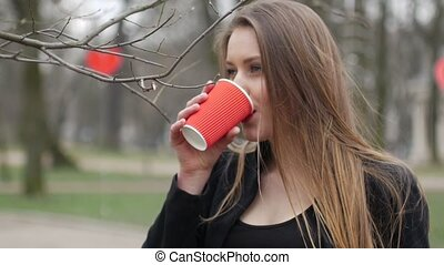 Portrait of beautiful young urban fashion girl in autumn park drinking cup of takeaway coffee