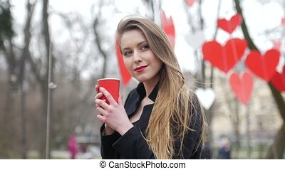 Young beautiful blonde hipster woman posing on the autumn park decorated with red paper hearts background with cup of takeaway coffee. Valentine's Day concept