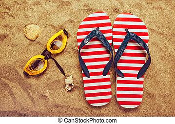 Pair of thongs or flip flops on beach sand - Pair of thongs...
