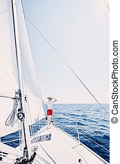 Girl on sailboat - Young woman wearing sunglasses and red...