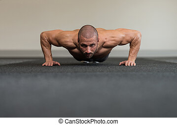 Young Bodybuilder Exercising Press Ups On Floor - Healthy...