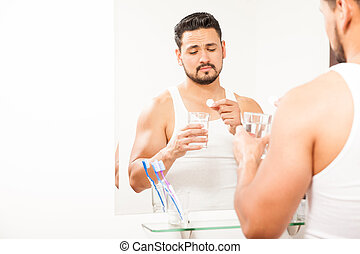 Hungover man taking a tablet in the morning