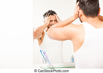 Young man waking up in front of a mirror