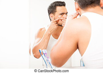 Young man squeezing a pimple - Good looking young man...