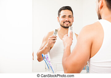 Hispanic young man shaving his beard - Portrait of a good...
