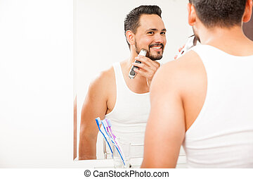 Young man shaving his beard and smiling - Portrait of an...