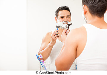 Happy young man shaving his beard - Handsome young man using...