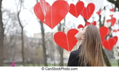 Beautiful young stylish girl plays with paper hearts decoration in the autumn park. Valentine's Day concept.