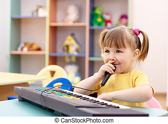 Girl play on a piano and sing in microphone - Little girl...