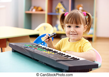 Girl with electronic piano and microphone - Little girl with...