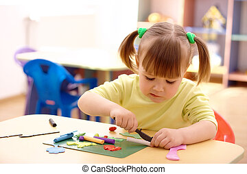 Little girl play with plasticine in preschool - Cute little...